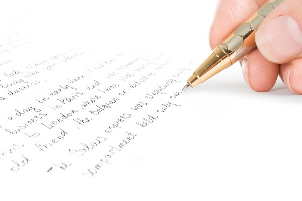 image of a hand using pen to write down words